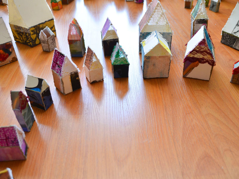Slideshow image by Jen Hamilton - art installation consisting of small house-like structures made from paper and cloth